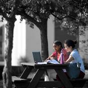 Two Jefferson students studying at a picnic table on the Campus Quad.