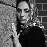 A young woman with large eyes and a scarf is resting her head and hand on the wall of a building. She looks directly into the camera with a calm and friendly expression.