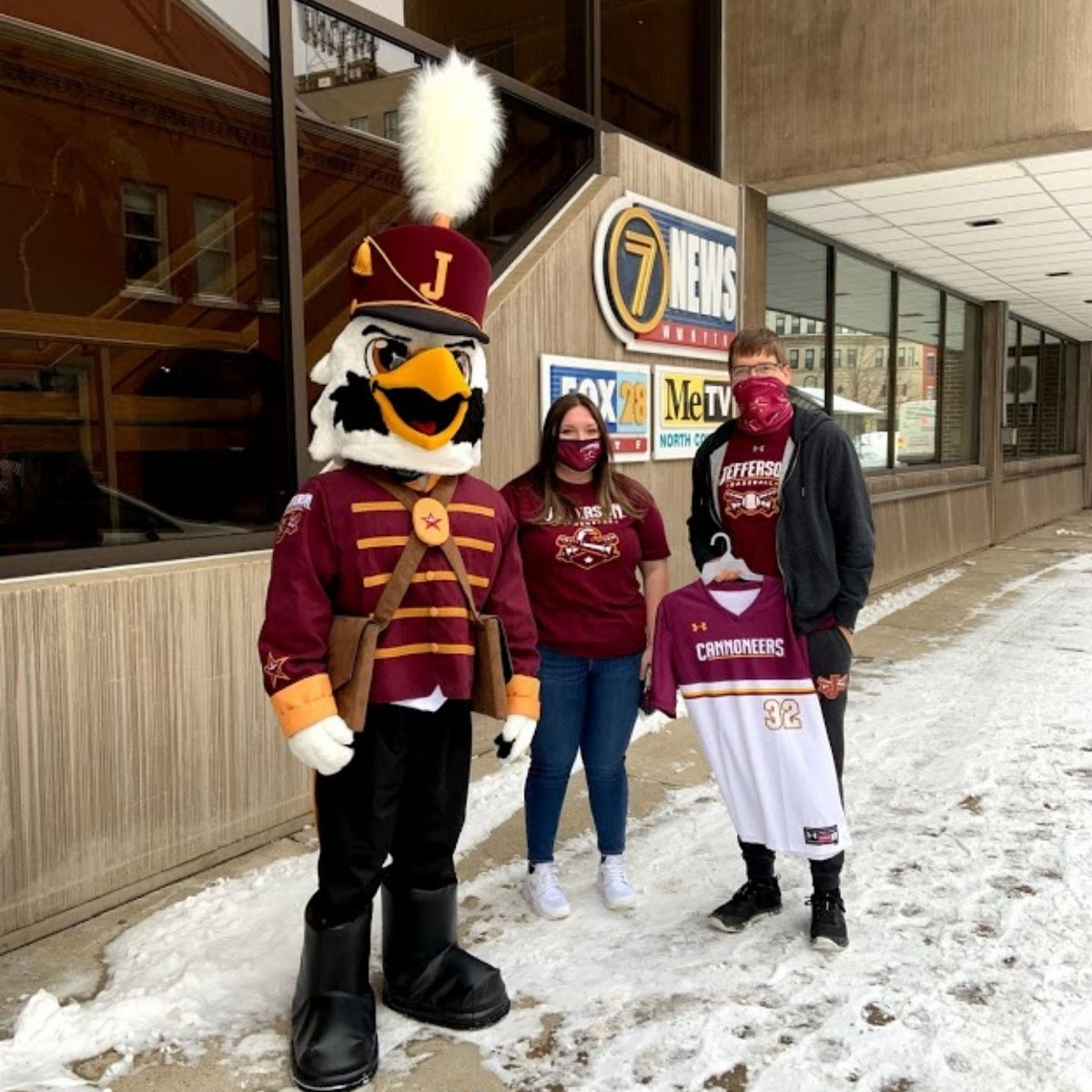 Bald Eagle in a Military Cannoneer Uniform with two student athletes standing outside television station